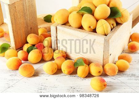 Ripe apricots in crate on wooden table, closeup