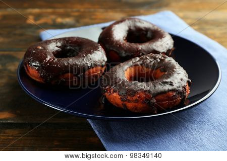 Delicious doughnuts with chocolate icing on table close up