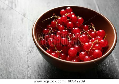 Ripe red currant  in bowl on wooden background
