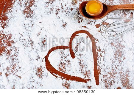 Wooden spoon with egg and corolla on flour background