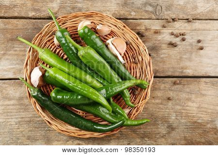 Green hot peppers with garlic on wooden table close up