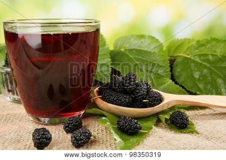 Glass of refreshing mulberry juice with berries on bright background