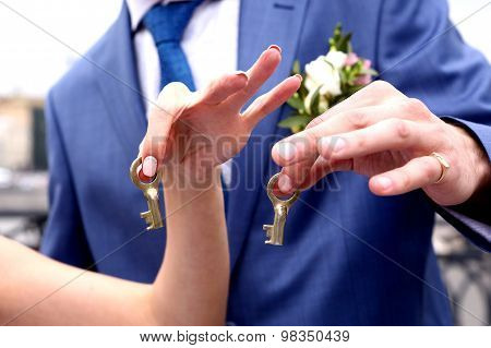 two keys in newlywed hands ready to throw  the river