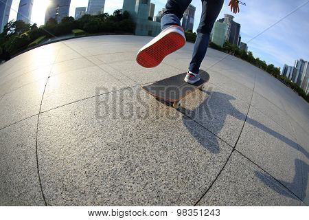skateboarder legs skateboarding at modern sunrise city