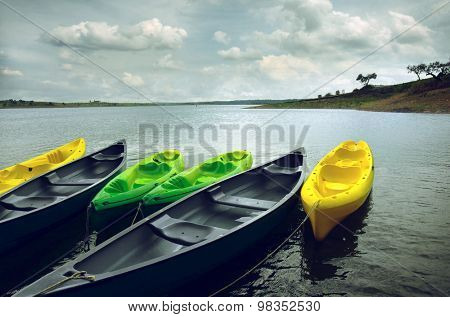 Green and yellow kayaks and canoes docked in the shore of a lake