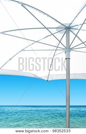 Calm beach scene with white sunshade near the blue sea