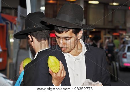 BENE - BERAK, ISRAEL - SEPTEMBER 17, 2013: A young religious man - Jew closely examining citrus - fruit for the holiday of Sukkot. The traditional holiday bazaar before Sukkot