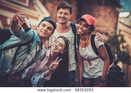 Multiracial friends tourists making selfie in an old city