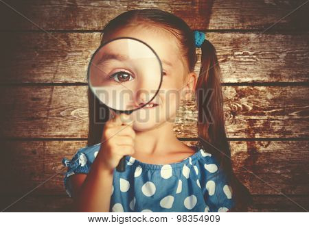 Child Girl Playing With Magnifying Glass In Detective