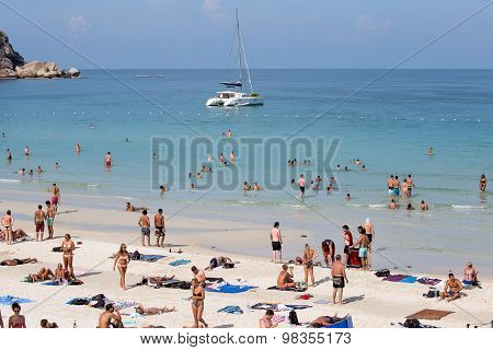 Guys and girls have a rest on Haad Rin beach before the Full Moon Party In Koh Phangan, Thailand