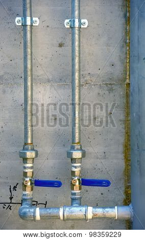 Galvanized steel tubes mounted on a concrete wall
