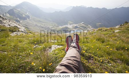 Legs of traveler sitting on a high mountain top in travel. Freedom concept