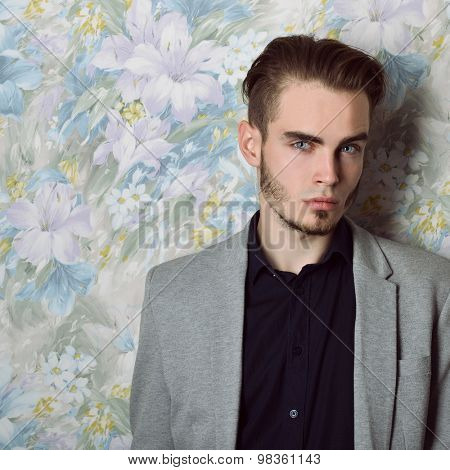 Portrait of attractive young mysterious man looking at camera, over floral background. Image toned.