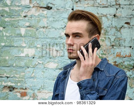 Portrait of young handsome man calling phone outdoor against grunge obsolete wall