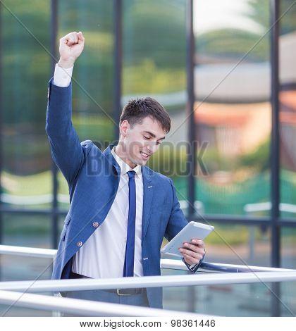 Successful confident businessman celebrates his success.