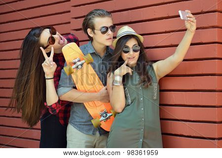 Young people having fun summer outdoor and making selfie with smart phone against red brick wall. Urban lifestyle, happiness, joy, friends, self photo concept. Image toned, noise added.