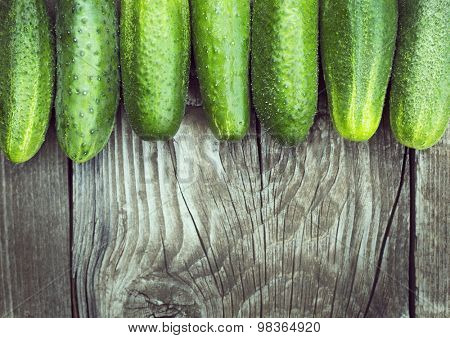 wood background with fresh cucumbers, space on the bottom for text