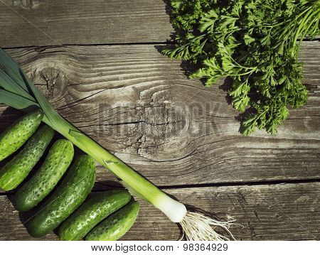 fresh green cucumbers, leek and parsley on old wood background