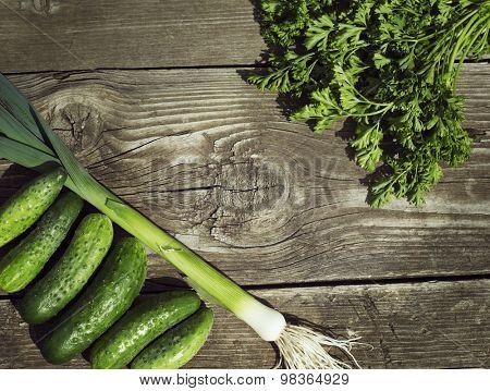 fresh green cucumbers, leek and parsley on old wood background