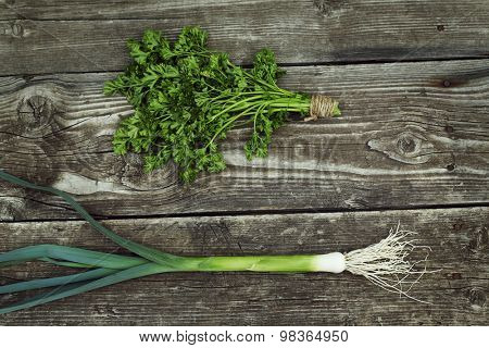 fresh green leek and parsley on old wood background