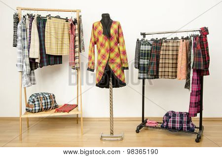 Dressing Closet With Plaid Clothes Arranged On Hangers And A Jacket On A Mannequin.