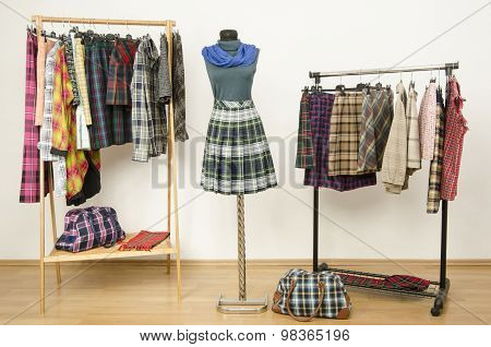 Dressing Closet With Plaid Clothes Arranged On Hangers And An Outfit On A Mannequin.