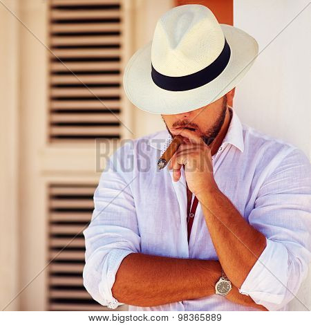 Confident Handsome Man Smoking Cigar, While Leaning On The Wall
