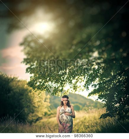 Romantic pregnant woman outside, among the trees and greenery like in fairytale.