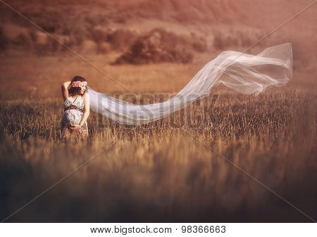 Romantic and beautiful pregnant woman outside in the field like a fairytale.