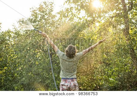 Man With Garden Hose Raises His Arms For Happiness