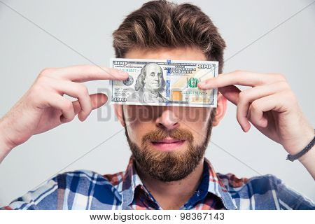 Portrait of a young man covering his eyes with bill of USA dollar isolated on a white background