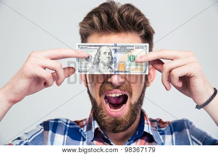 Portrait of a man covering his eyes with bill of USA dollar and shouting isolated on a white background
