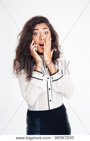 Surprised businesswoman talking on the phone isolated on a white background