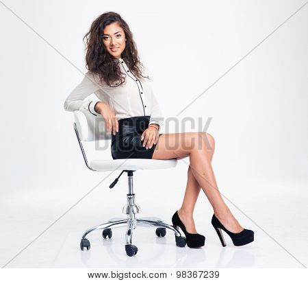 Smiling businesswoman sitting on the office chair isolated on a white background and looking at camera