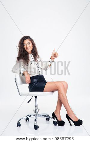 Happy young businesswoman sitting on the office chair and showing thumb up isolated on a white background