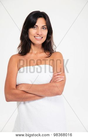 Portrait of a smiling charming woman standing with arms folded isolated on a white background. Looking at camera