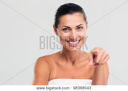 Portrait of a smiling woman in towel pointing finger at camera isolated on a white background
