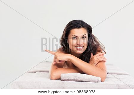 Happy woman lying on massage lounger and pointing finger away. Looking at camera