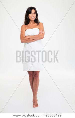 Full length portrait of attractive happy woman in towel standing with hands folded isolated on a white background. Looking at camera