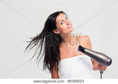 Pretty young woman in towel drying her hair isolated on a white background