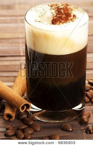 espresso with milk froth cocoa powder and cinnamon sticks