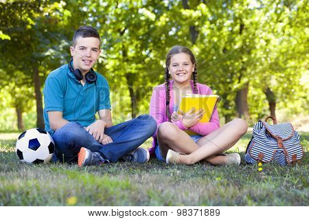 Happy smart kids sitting at the park