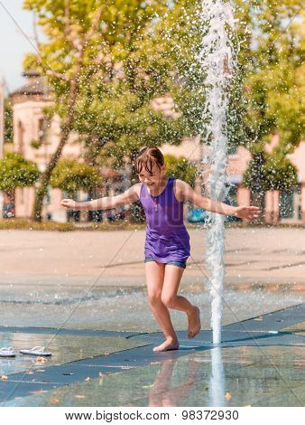 Hot summer in the city - girl is enjoying fountain with cold water