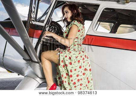 Pilot, beautiful woman with pinup style colourful dress, along with vintage aircraft