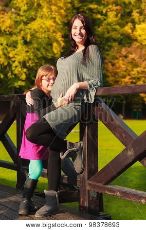 Pregnant Woman With Her Daughter In Park Outdoor