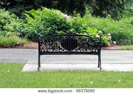 Black ornate bench in a park