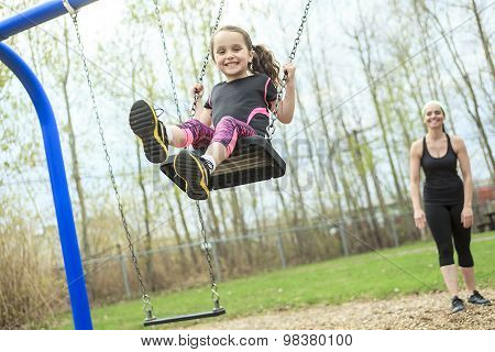 Mother swinging her daughter