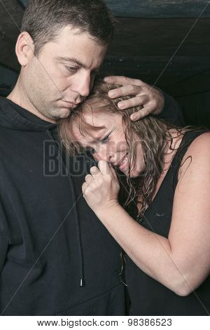 men consoling woman and trying to calm down.