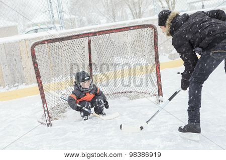 A father playing at the skating rink in winter.
