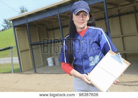 A baseball instructor holding a note pad.